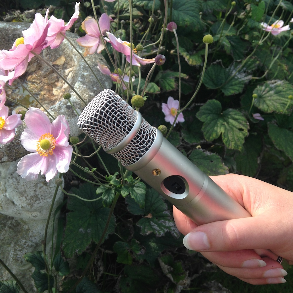 photo of a hand holding a microphone in amongst a bed of flowers