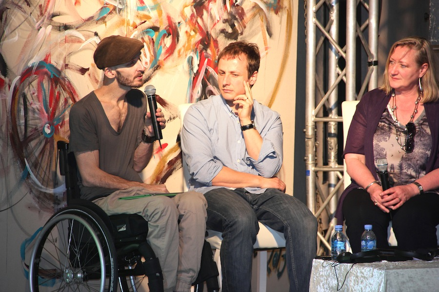 photo of wheelchair dancer Mark Brew on stage with animator Joel Simon and British Council representative Carole McFadden