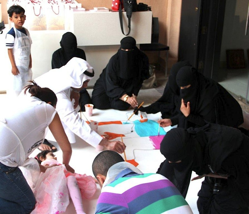 A group of women dressed in burkas and a man in white islamic head dress, sit painting with artist Rachel Gadsden outside an art gallery