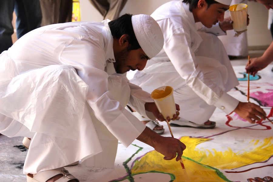 photo of a group of muslim men crouching down to paint a mural on the floor