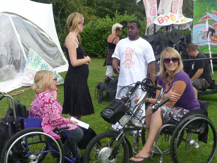 photo of two women in wheelchairs on the grass with several carnival performers in the background