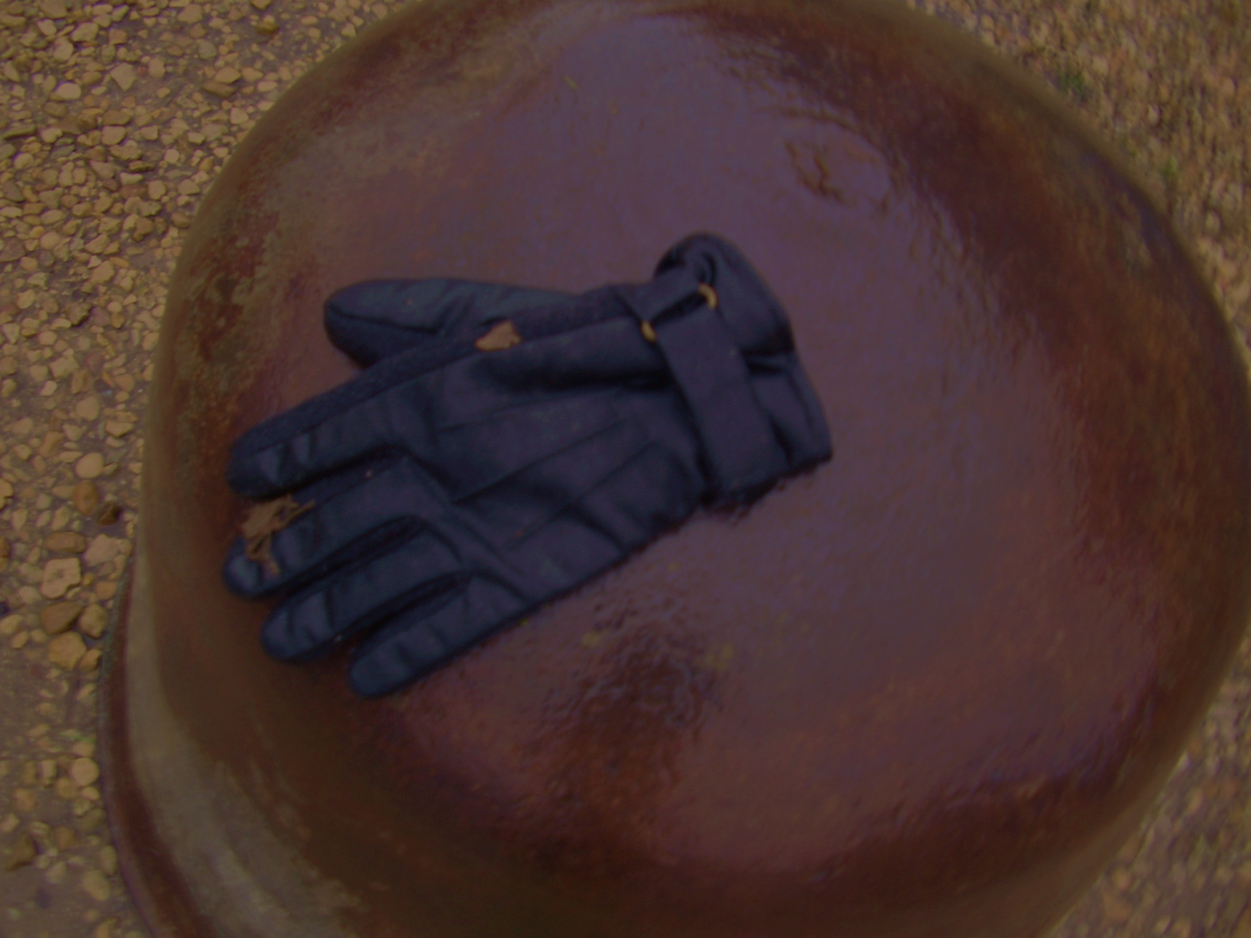 Colour photograph of a stray glove placed on a steel traffic bollard in a car park in Lacock.