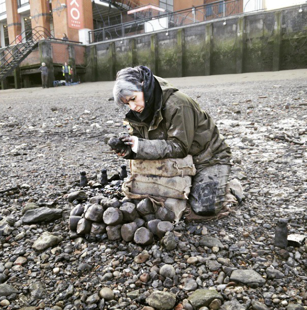 Liz Crow crouched on the stoney Thames foreshore sculpting small clay figures