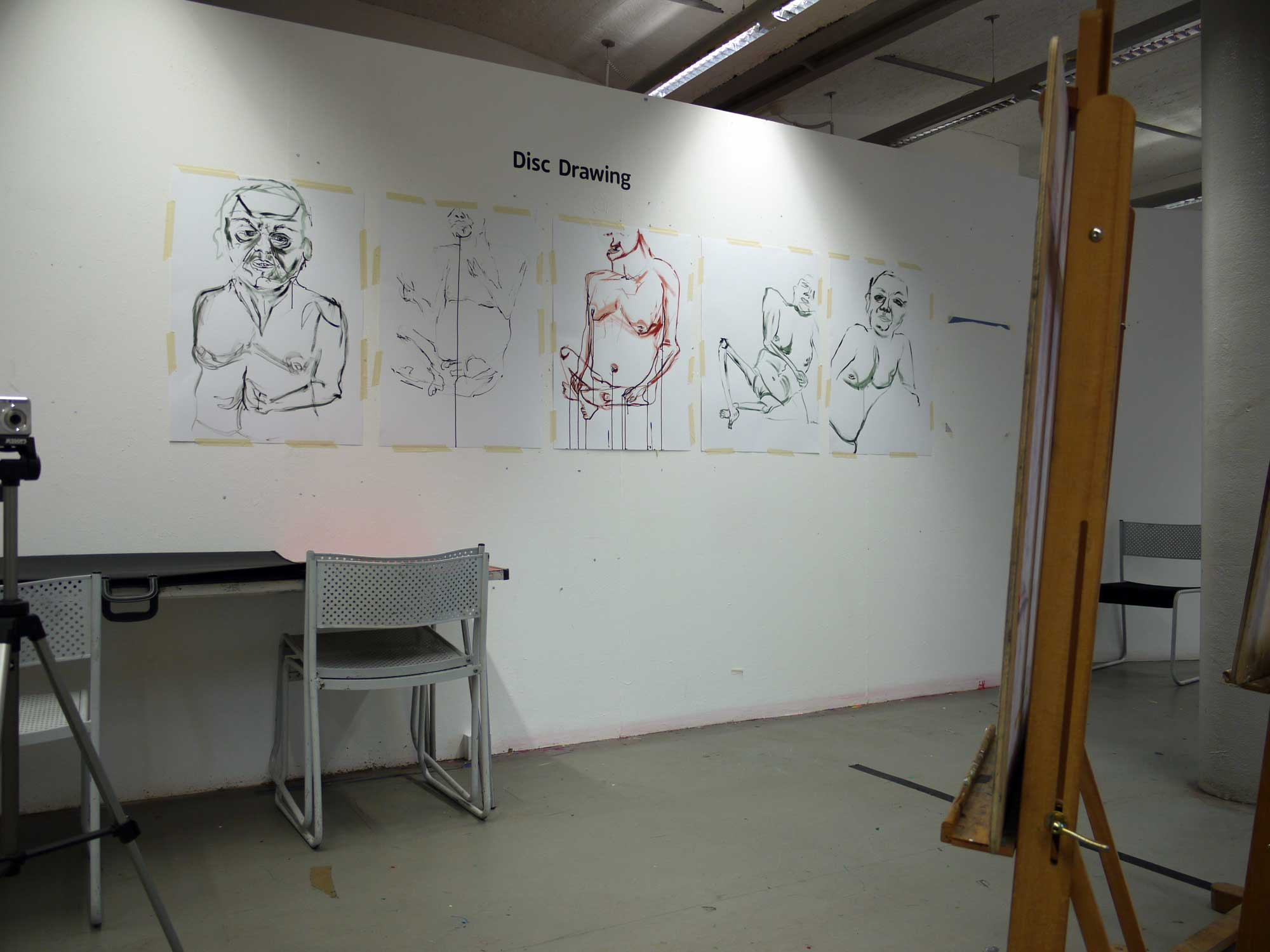 a series of portrait drawings on the wall of the artists' studio