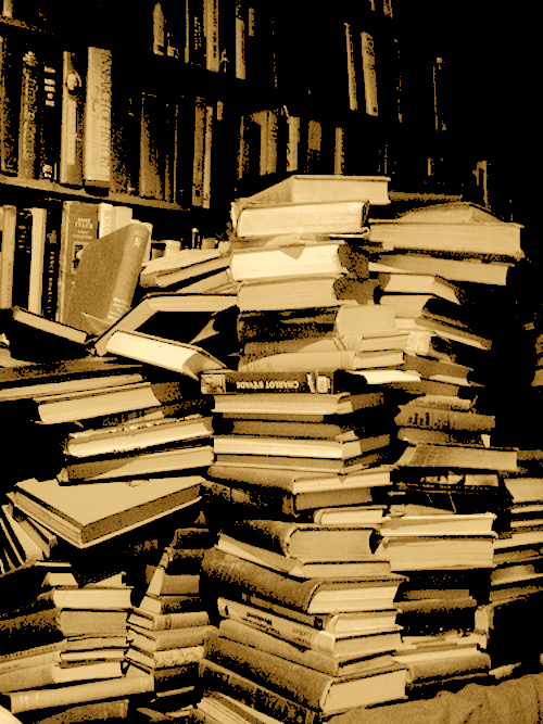 stacks of black and white books with a sepia tint