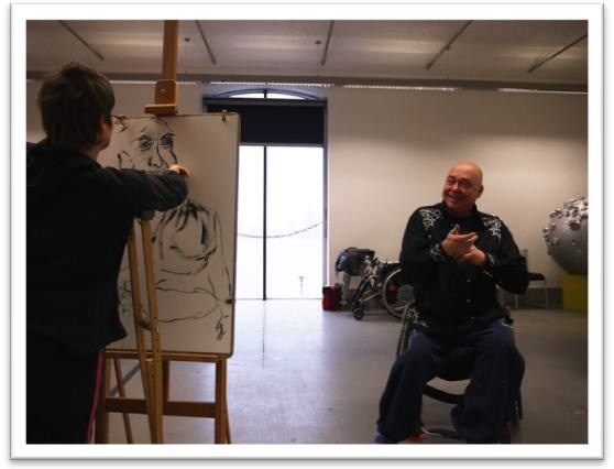 photo of woman artist drawing a man in a studio setting